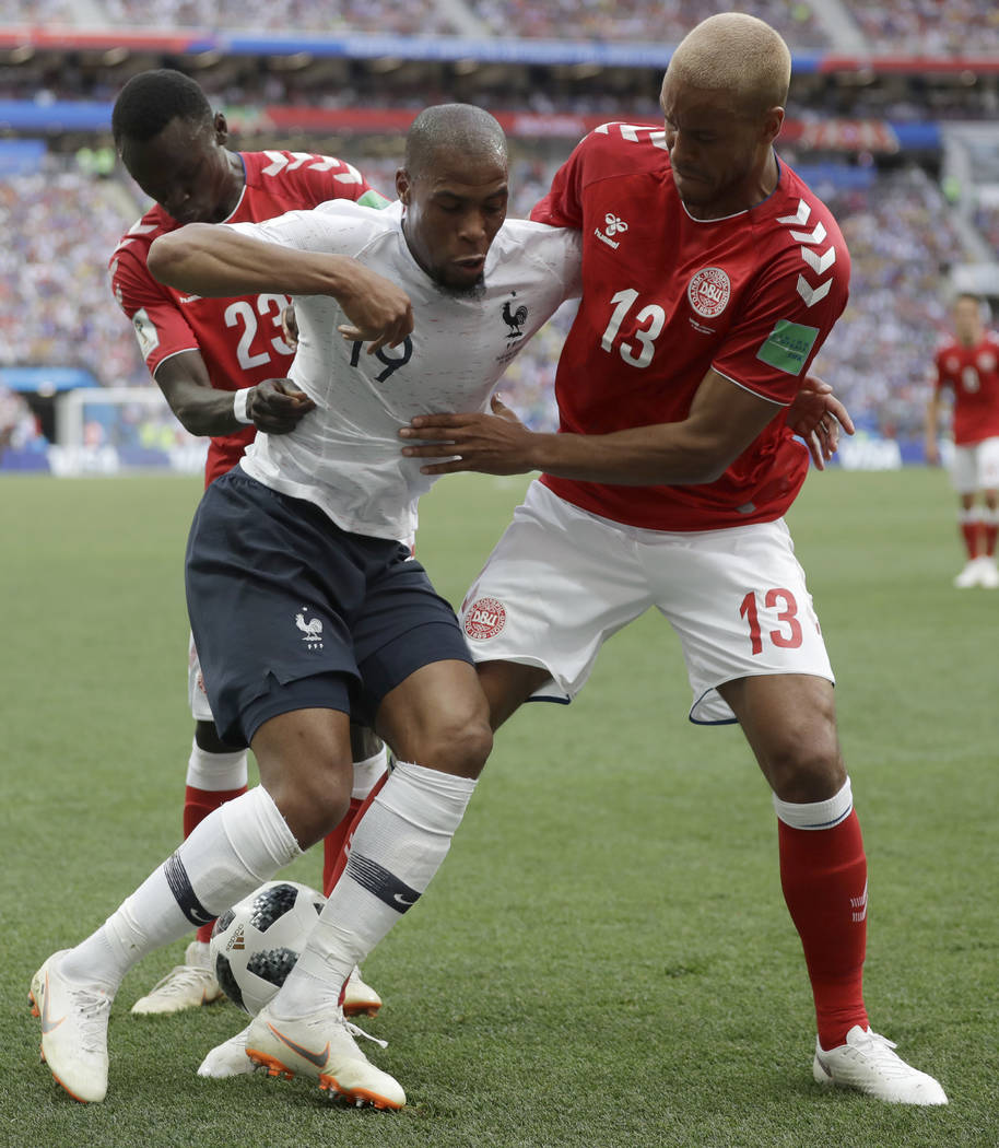 France's Djibril Sidibe, centre is tackled by Denmark's Pione Sisto, left, and Denmark's Mathias Jorgensen during the group C match between Denmark and France at the 2018 soccer World Cup at the L ...