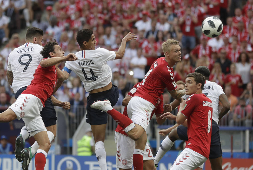 Denmark's Simon Kjaer, top centre right, heads the ball under pressure from France's Raphael Varane top center left, during the group C match between Denmark and France at the 2018 soccer World Cu ...