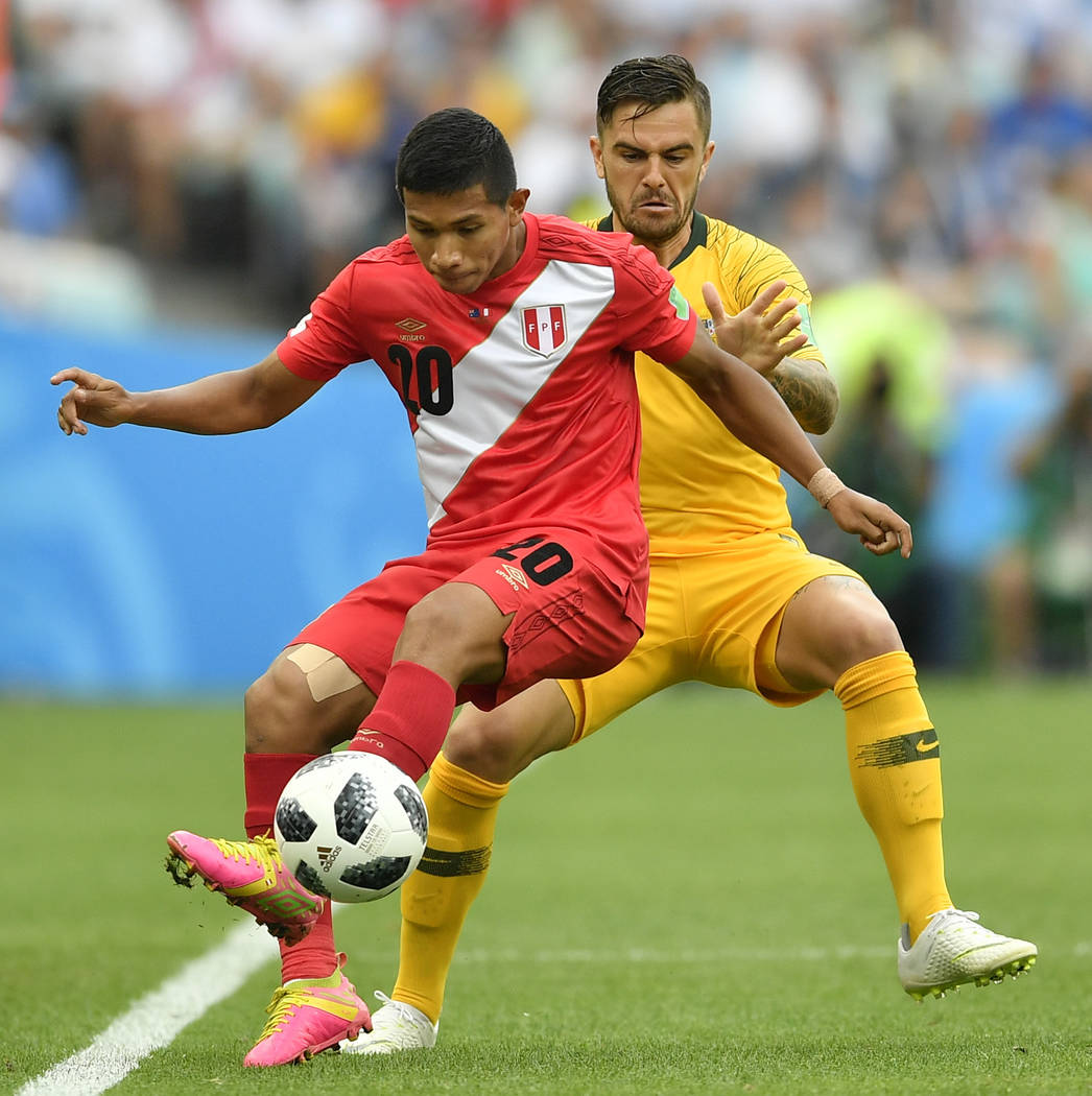 Peru's Edison Flores, left, and Australia's Joshua Risdon challenge for the ball during the group C match between Australia and Peru, at the 2018 soccer World Cup in the Fisht Stadium in Sochi, Ru ...