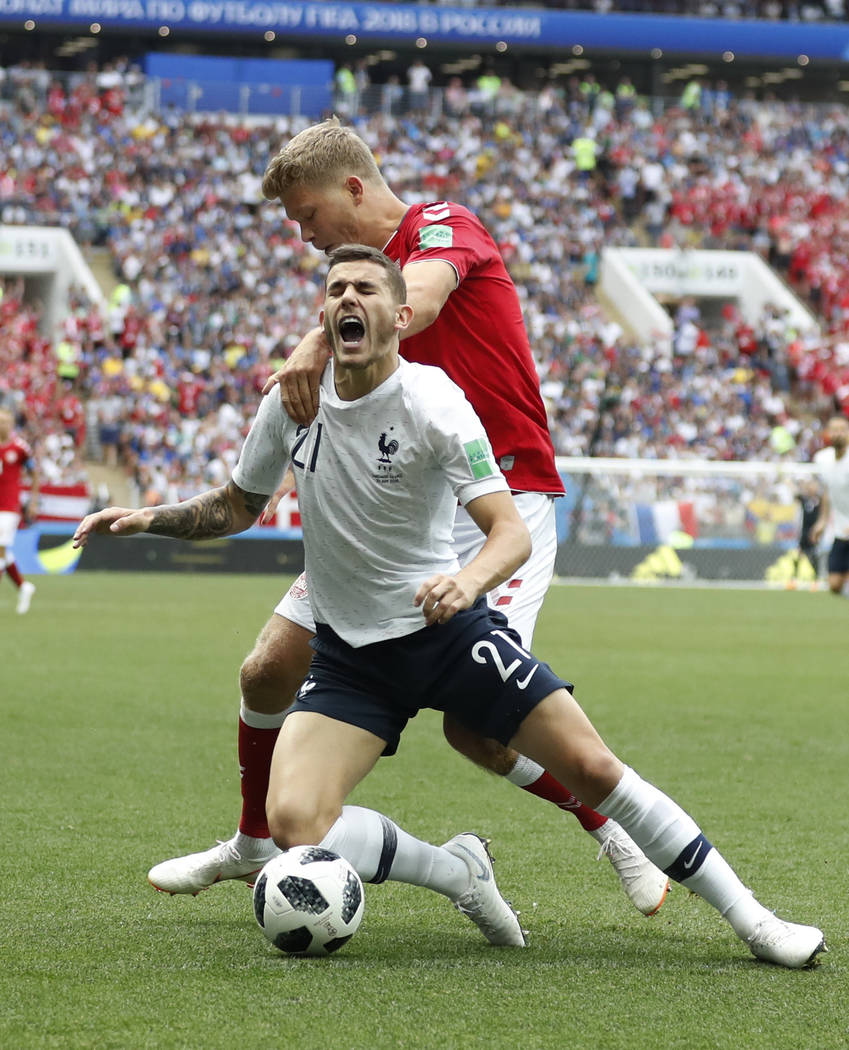 Denmark's Andreas Cornelius, top, vies for the ball with France's Lucas Hernandez during the group C match between Denmark and France at the 2018 soccer World Cup at the Luzhniki Stadium in Moscow ...