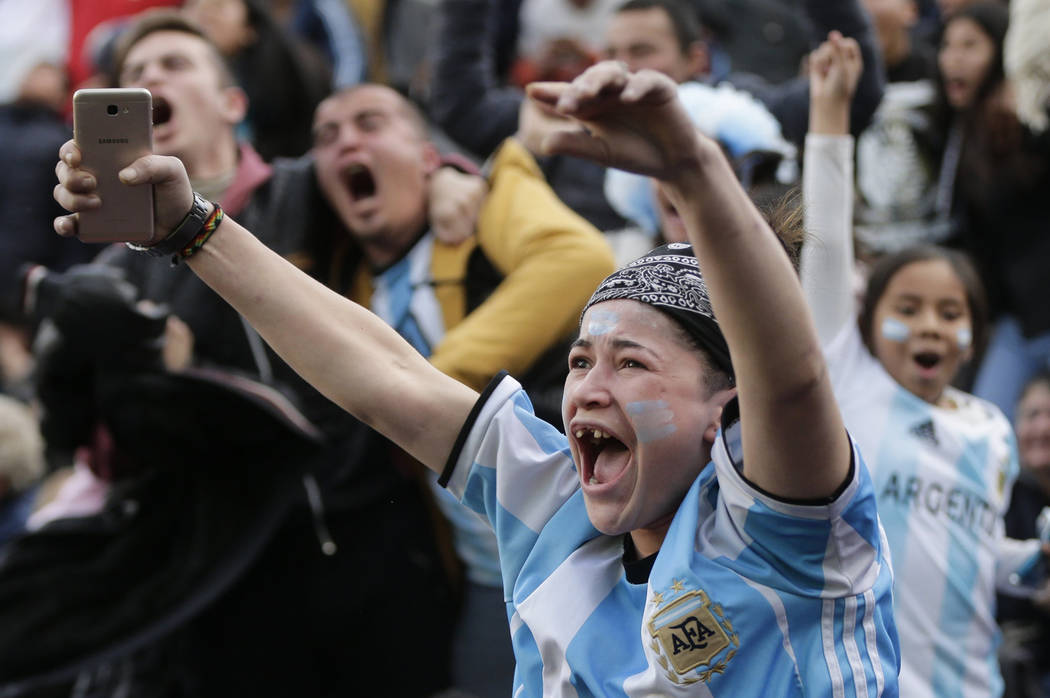 Soccer fans celebrate Argentina's goal, by player Marcos Rojo, during a live broadcast of the Russia 2018 World Cup soccer match against Nigeria, in Buenos Aires, Argentina, Tuesday, June 26, 2018 ...