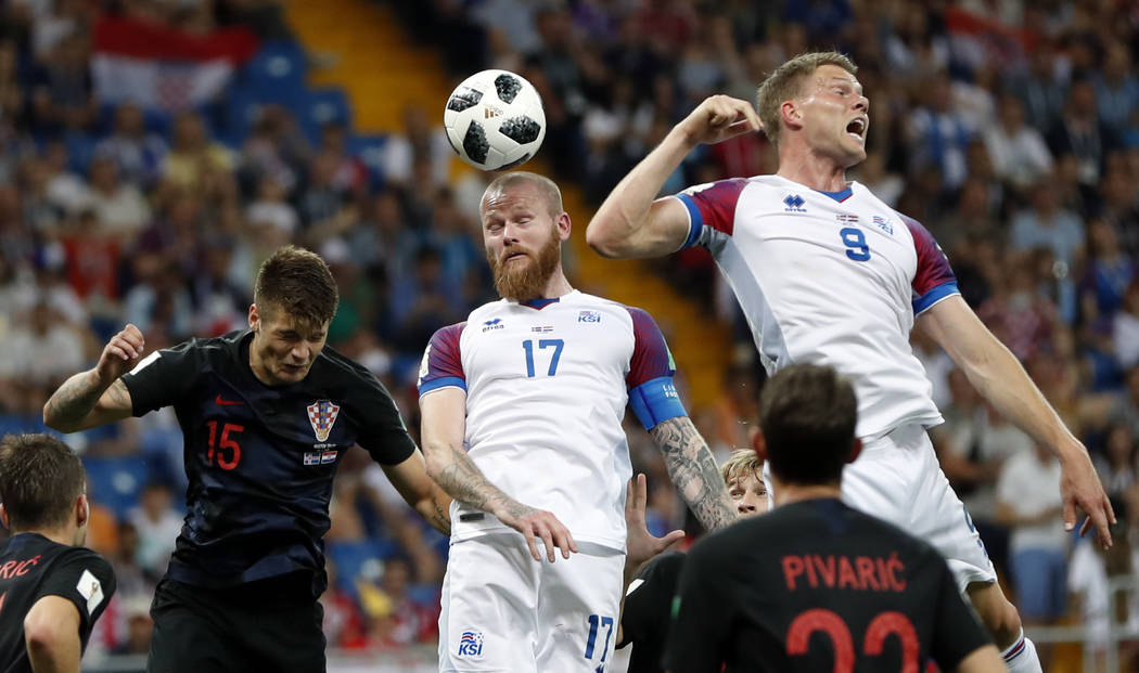 From left, Croatia's Duje Caleta-Car, Iceland's Aron Gunnarsson and Iceland's Bjorn Sigurdarson jump for the ball during the group D match between Iceland and Croatia, at the 2018 soccer World Cup ...