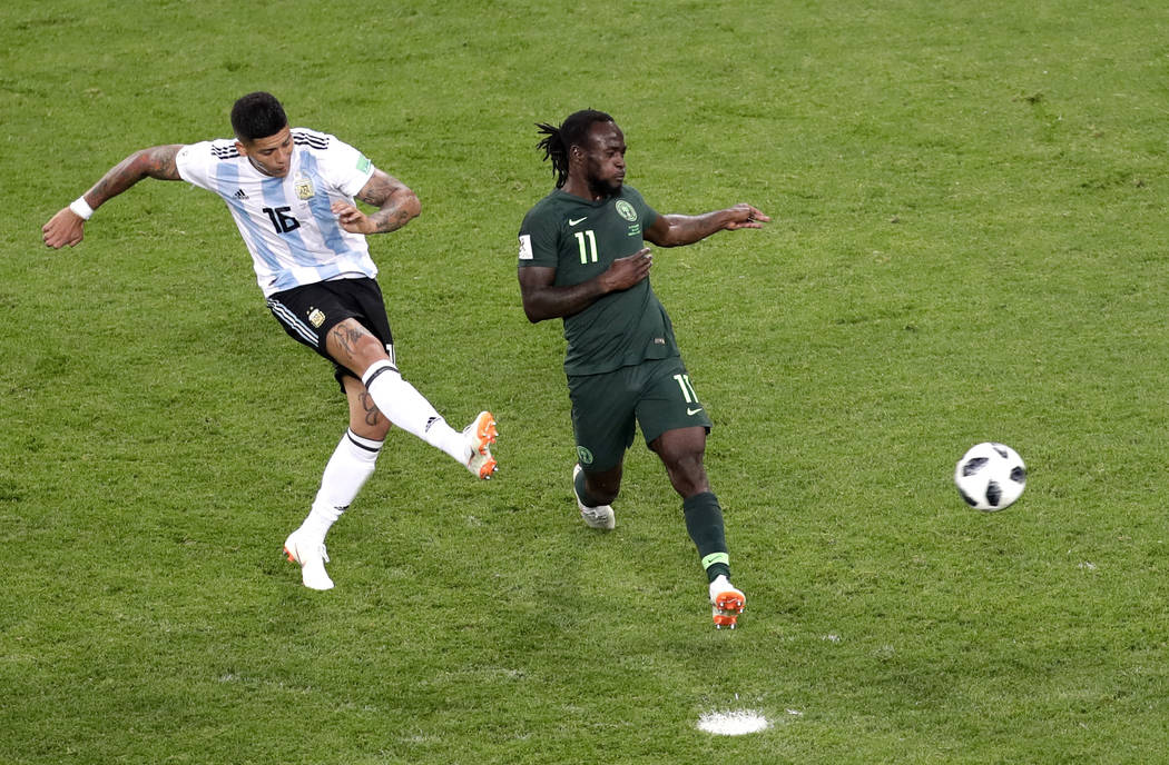 Argentina's Marcos Rojo, left, scores his side's second goal past Nigeria's Victor Moses during the group D match between Argentina and Nigeria, at the 2018 soccer World Cup in the St. Petersburg ...