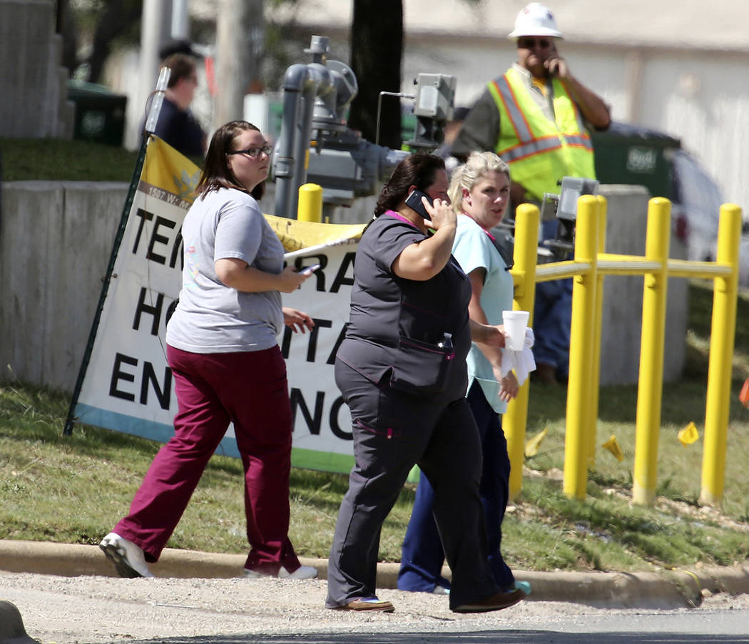 People walk to the rear of Coryell Memorial Healthcare System hospital where an explosion in a building under construction injured several people, and knocked power out for a large portion of the ...