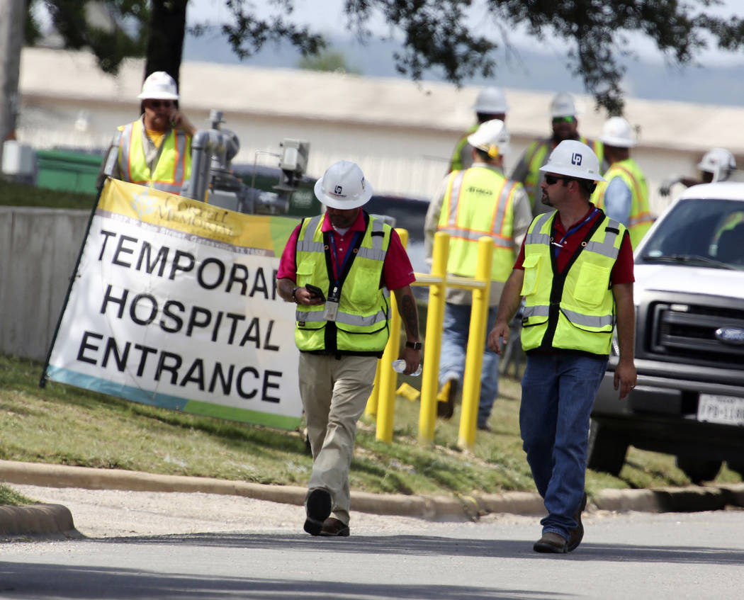 Construction workers leave a temporary entrance to Coryell Memorial Healthcare System hospital where an explosion in a building under construction injured several people, and knocked power out for ...
