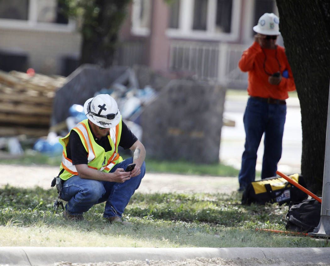 A construction worker checks his phone near Coryell Memorial Healthcare System hospital where an explosion in a building under construction injured several people, and knocked power out for a larg ...