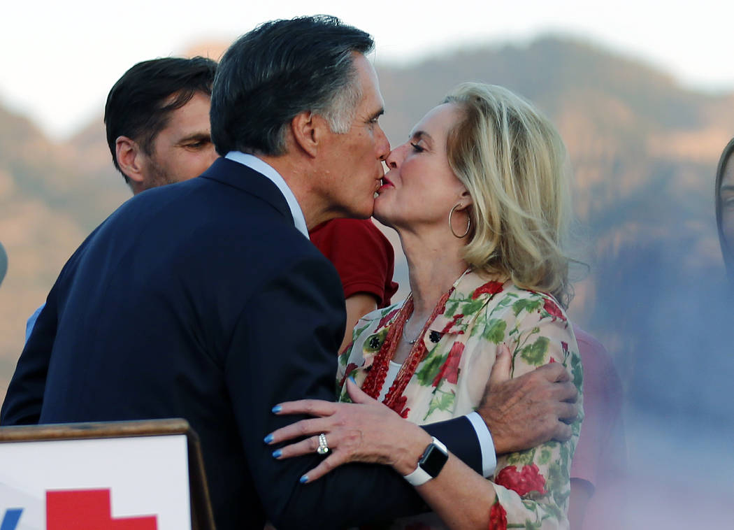 Former GOP presidential nominee Mitt Romney kisses his wife, Ann, after addressing supporters at their campaign headquarters during a primary election night party, Tuesday, June 26, 2018, in Orem, ...