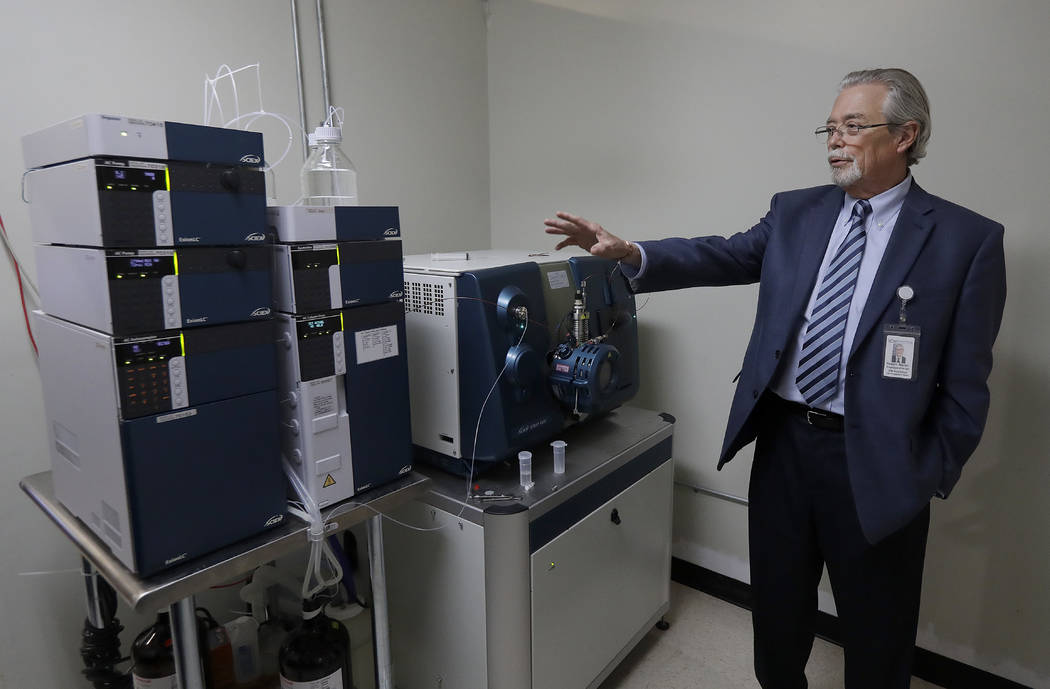In this June 21, 2018, photo, Robert Martin, co-founder and CEO of CW Analytical Laboratories, is interviewed next to an instrument capable of analyzing small organic molecules to look for pestici ...