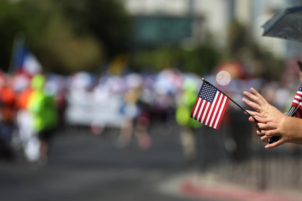 An spectator holding an American flag watches the Lions Clubs International Parade of Nations on S. 4th Street in Las Vegas, Saturday, June 30, 2018. Erik Verduzco Las Vegas Review-Journal @Erik_V ...