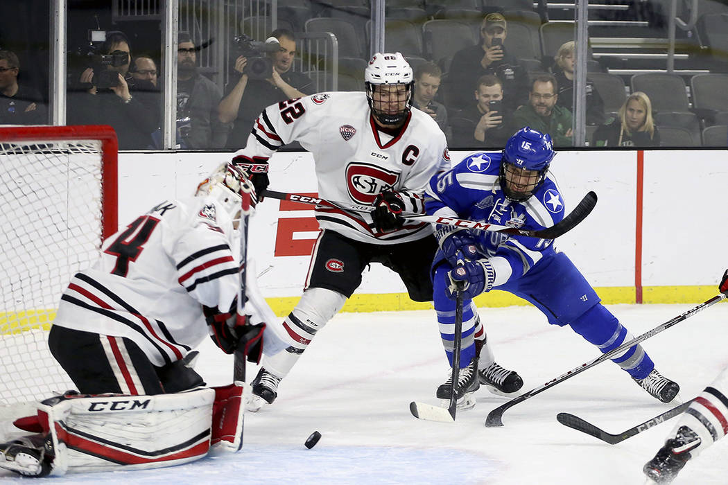 Air Force's Evan Giesler (15) battles to get the puck past St. Cloud State goalie David Hrenak (34) as teammate Jimmy Schuldt (22) defends during the first period of an NCAA regional men's college ...