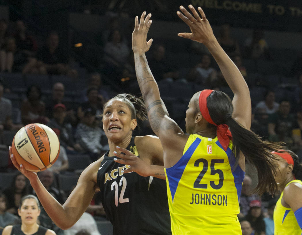 Aces center A'ja Wilson (22) drives past Dallas Wings forward Glory Johnson (25) in the 2nd quarter on Wednesday, June 27, 2018, at the Mandalay Bay Events Center, in Las Vegas. Benjamin Hager Las ...