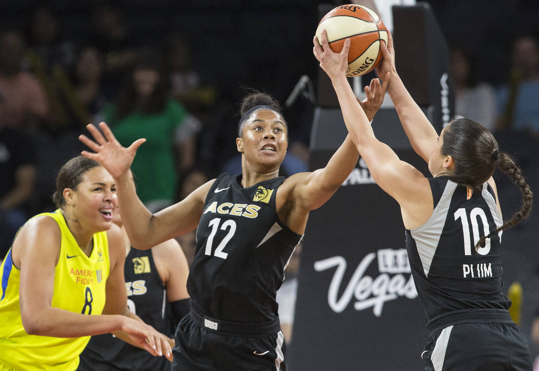 Aces forward Nia Coffey (12) and guard Kelsey Plum (10) reach for a loose ball in the 3rd quarter during their matchup with the Dallas Wings on Wednesday, June 27, 2018, at the Mandalay Bay Events ...