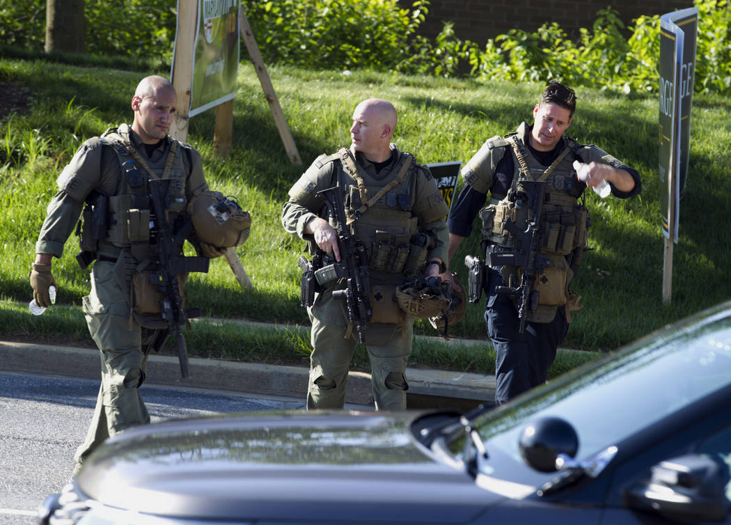 Police officers walk at the scene after multiple people were shot at a newspaper's office building in Annapolis, Md., Thursday, June 28, 2018. A single shooter killed several people Thursday and w ...