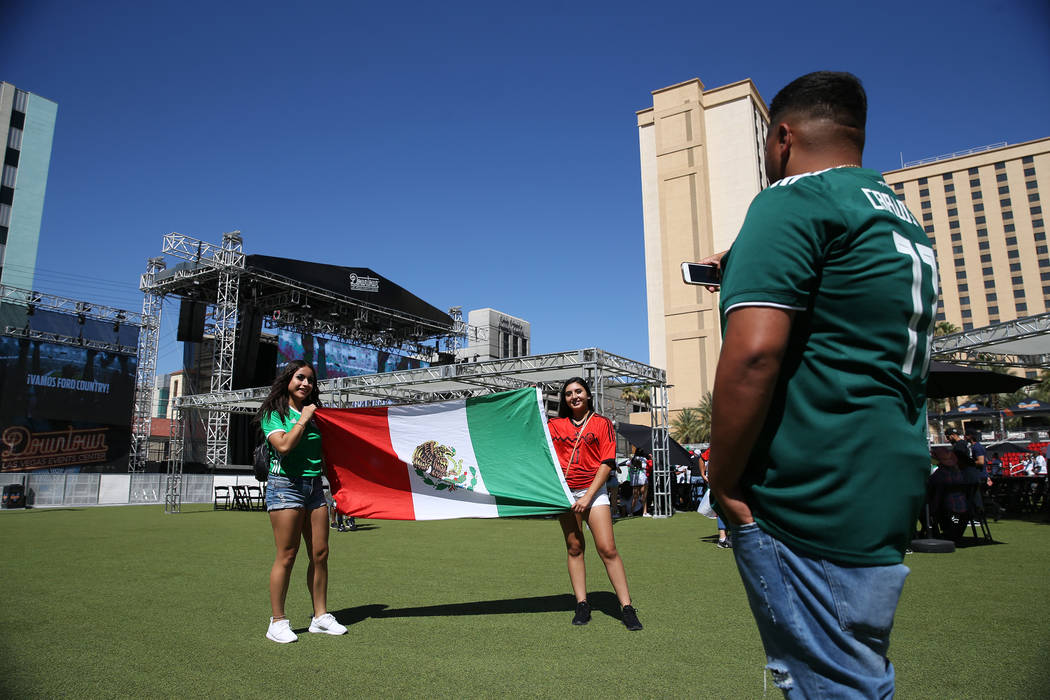 Alejandro Montes takes a photo of his friends Yadira Ruelas, left, and Helena Hernandez, right, during a watch party for the World Cup soccer match between Mexico and South Korea at the Downtown L ...