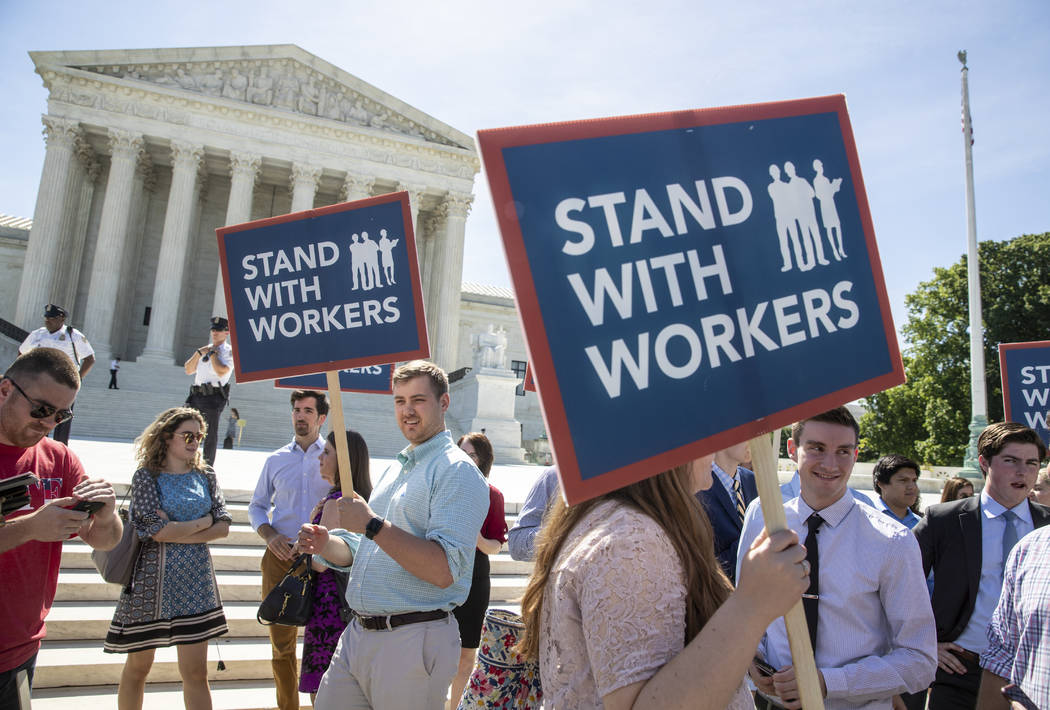 People gather at the Supreme Court awaiting a decision in an Illinois union dues case, Janus vs. AFSCME, in Washington, Monday, June 25, 2018. The Supreme Court says government workers can't be fo ...