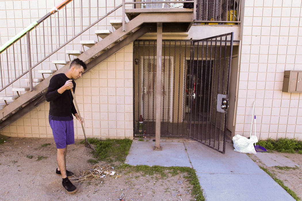 Jacob Edward Delgado, 23, rakes up debris outside his family's Las Vegas apartment Friday, March 16, 2018. Delgado said that he was put in a headlock and sedated at North Vista Hospital after he a ...