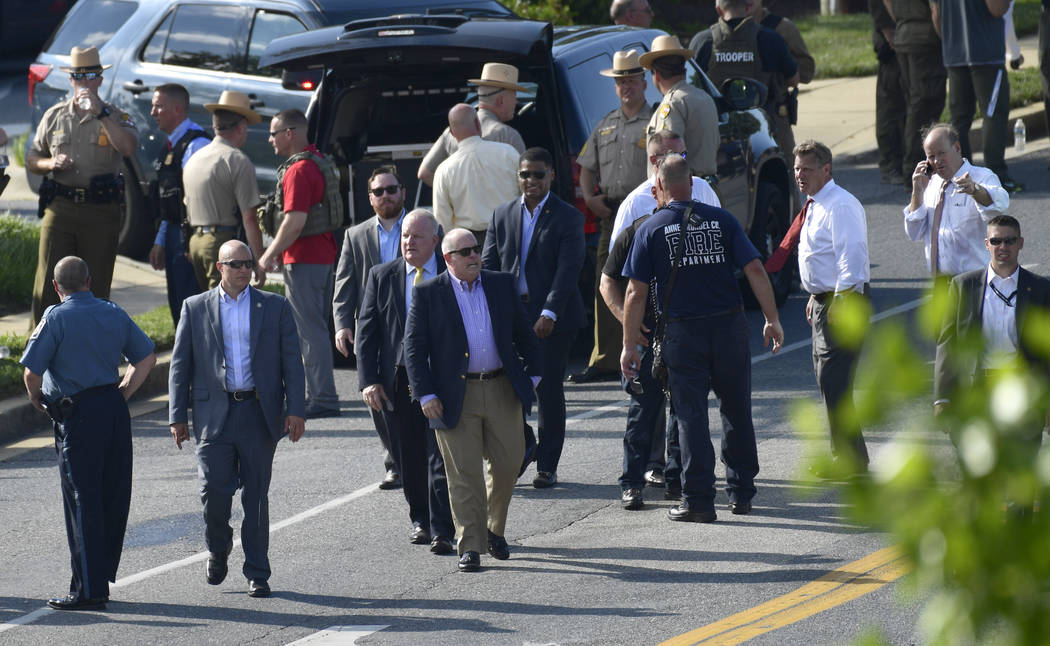 Maryland Gov. Larry Hogan, center in sunglasses, surveys the scene of a shooting in Annapolis, Md., Thursday, June 28, 2018. (AP Photo/Susan Walsh)