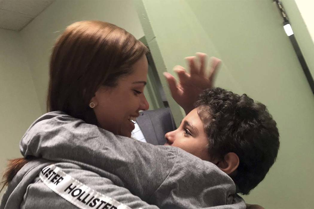 In this Tuesday, June 26, 2018 photo provided by paralegal Luana Mazon, Lidia Karine Souza, 27, hugs her 9-year-old son Diogo De Olivera Filho as Souza visited her son for the first time since the ...