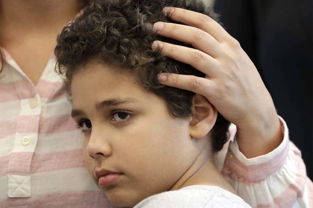Lidia Karine Souza runs her hand through her son Diogo De Olivera Filho's hair, at the Mayer Brown law firm during a news conference shortly after Diogo was reunited with his mother Thursday, June ...