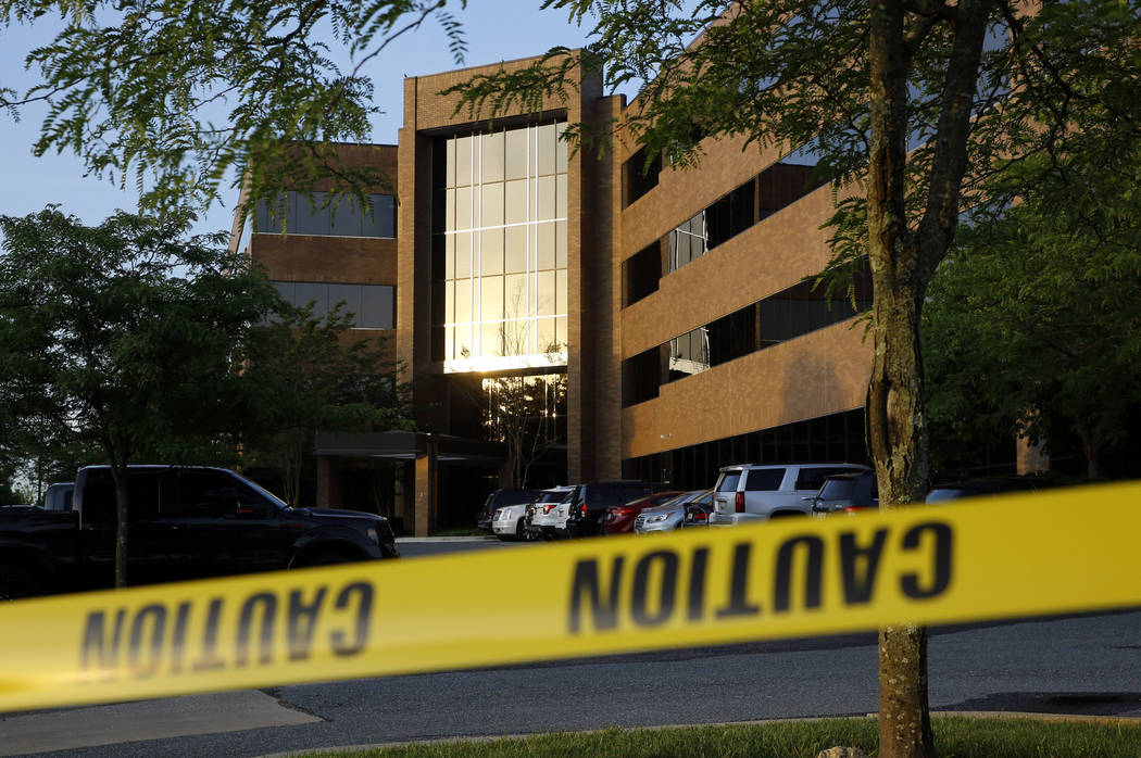 Crime scene tape surrounds a building housing The Capital Gazette newspaper's offices, Friday, June 29, 2018, in Annapolis, Md. A man armed with smoke grenades and a shotgun attacked journalists i ...