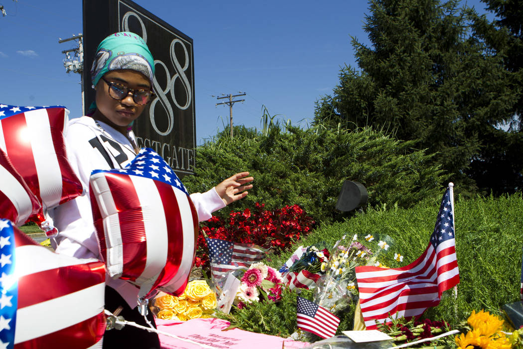 Neighbor Nina Larkins, 14, place flowers at the scene were five journalist were shot at their newspaper office in Annapolis, Md., Friday, June 29, 2018. A man armed with smoke grenades and a shotg ...