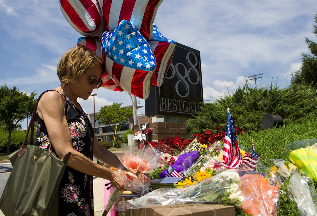 Neighbor Elly M. Tierney places flowers at a makeshift memorial at the scene outside the office building housing The Capital Gazette newspaper in Annapolis, Md., on Friday, June 29, 2018. A man ar ...