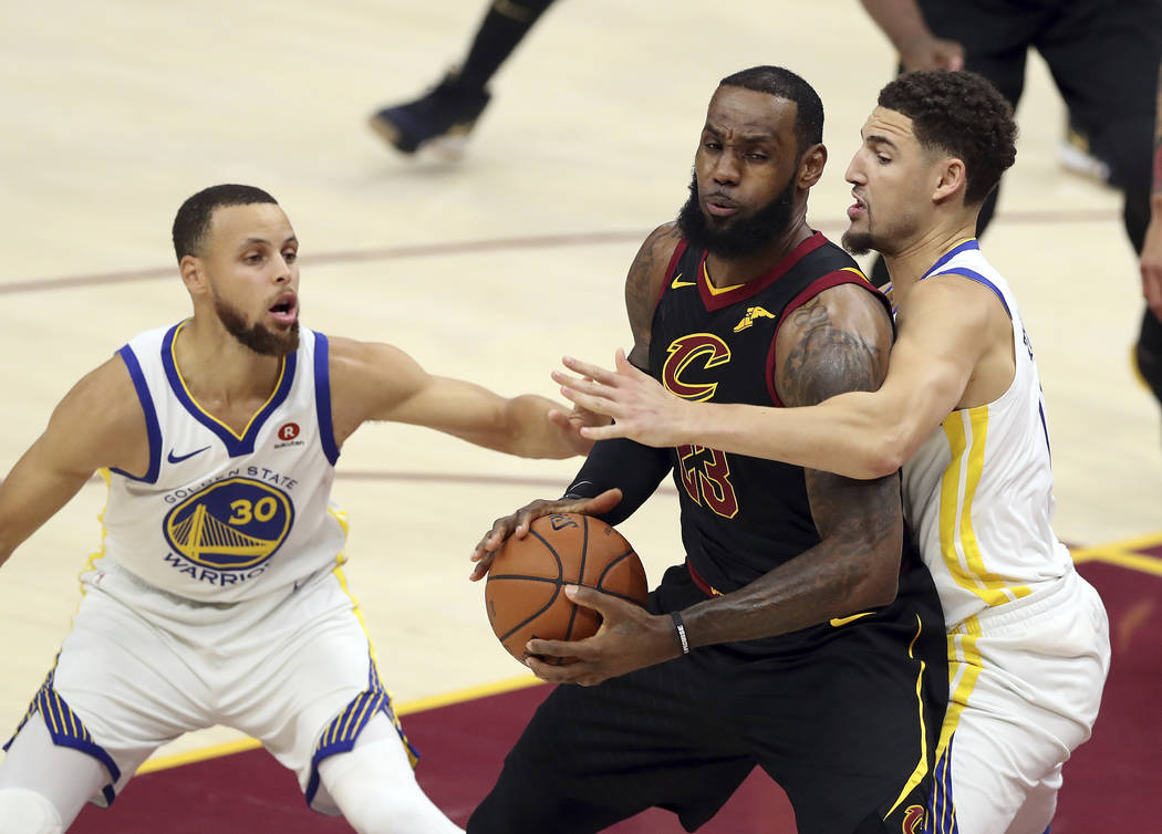 Cleveland Cavaliers' LeBron James (23) is defended by Golden State Warriors' Klay Thompson and Stephen Curry (30) during the first half of Game 4 of basketball's NBA Finals, Friday, June 8, 2018, ...