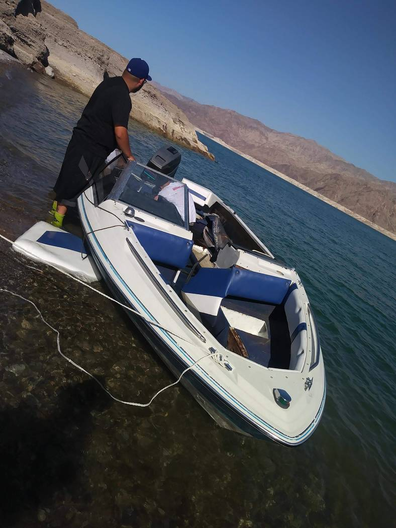 Juan Garcia helps drag his boat out of Lake Mead on Monday morning. Brian Estarza was driving the boat when it capsized early Sunday morning. National Park Service rangers rescued 17 people, inclu ...