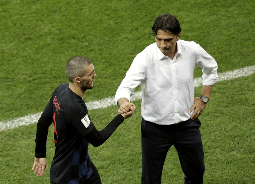 Croatia's Mateo Kovacic, left, shakes hand with Croatia head coach Zlatko Dalic as he domes off the field during the group D match between Iceland and Croatia, at the 2018 soccer World Cup in the ...
