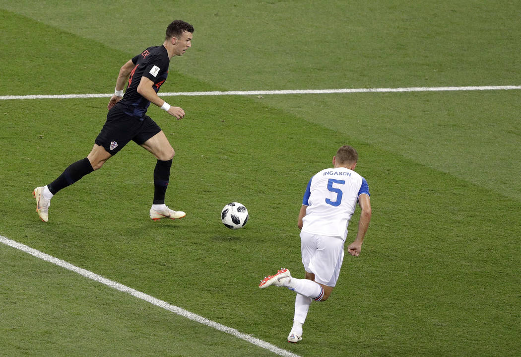 Croatia's Ivan Perisic left controls the ball to score his site's second goal as Iceland's Sverrir Ingason runs during the group D match between Iceland and Croatia at the 2018 soccer World Cup