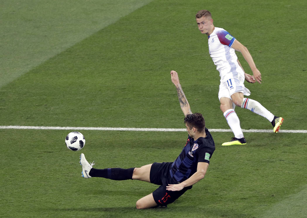 Iceland's Alfred Finnbogason, right, shoots the ball as Croatia's Duje Caleta-Car tries to defend during the group D match between Iceland and Croatia, at the 2018 soccer World Cup in the Rostov A ...