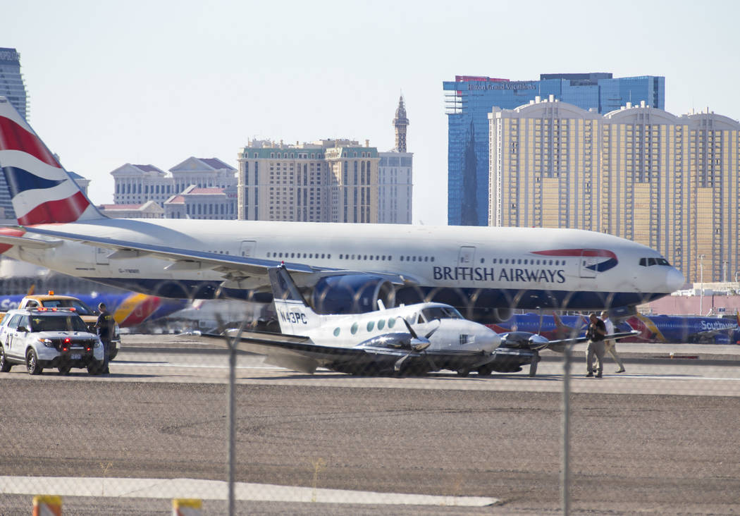 Personnel investigates a small passenger plane on its belly on a runway at McCarran International Airport in Las Vegas on Friday, June 29, 2018. Richard Brian Las Vegas Review-Journal @vegasphotograph