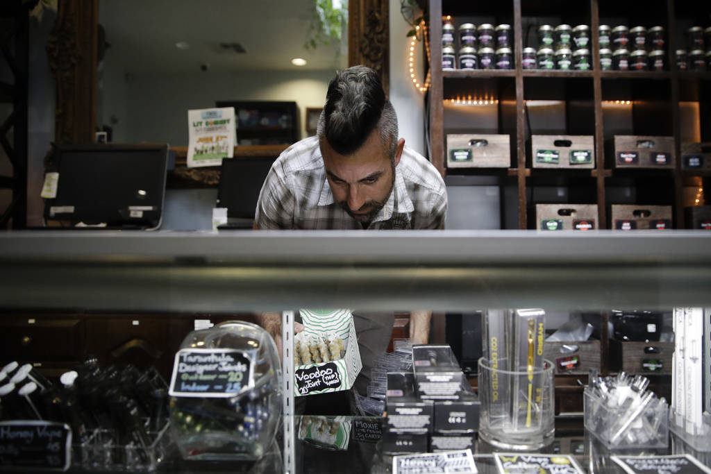 Jerred Kiloh, owner of the Higher Path medical marijuana dispensary, stocks shelves with with cannabis products in Los Angeles in June 2017. (AP Photo/Jae C. Hong)