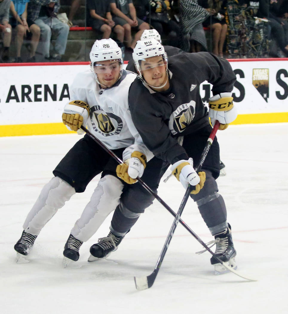 Vegas Golden Knights prospects Erik Brannstrom, left, and Tyler Wong fight for the puck during a scrimmage game at Golden Knights development camp at City Center Arena on Friday, June 29, 2018, in ...