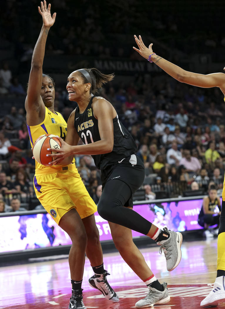 Las Vegas Aces center A'ja Wilson (22) gets fouled by Los Angeles Sparks center Jantel Lavender (42) as she goes up for a shot during the first half of a WNBA basketball game at the Mandalay Bay E ...