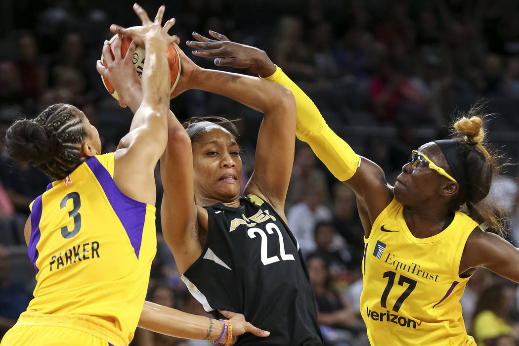 Las Vegas Aces center A'ja Wilson (22), center, is pressured by Los Angeles Sparks forwards Candace Parker (3) and Essence Carson (17) during the first half of a WNBA basketball game at the Mandal ...