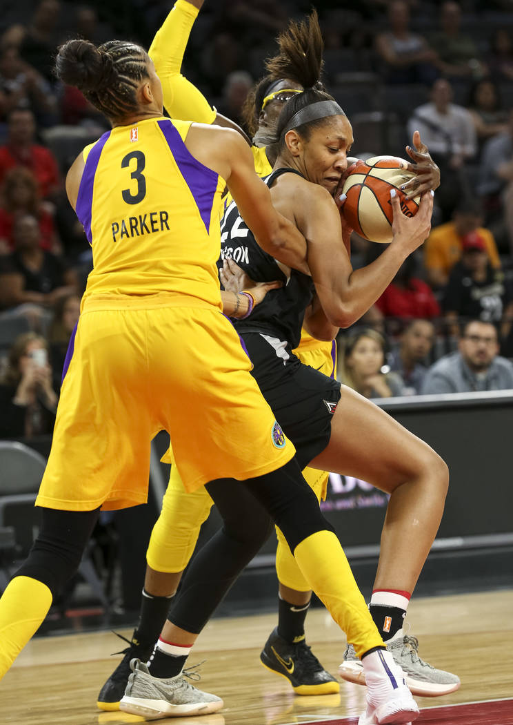 Los Angeles Sparks forwards Candace Parker (3), left, and Essence Carson (17), background, pressure Las Vegas Aces center A'ja Wilson (22) during the first half of a WNBA basketball game at the Ma ...