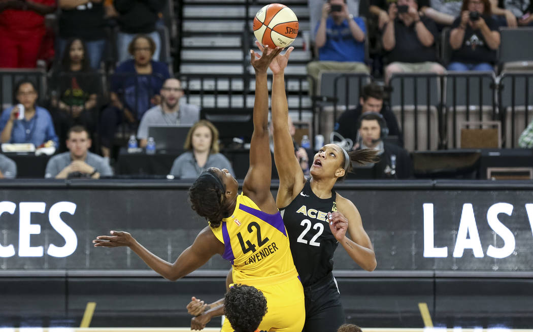 Los Angeles Sparks center Jantel Lavender (42) and Las Vegas Aces center A'ja Wilson (22) tip off at the start of a WNBA basketball game at the Mandalay Bay Events Center in Las Vegas on Friday, J ...