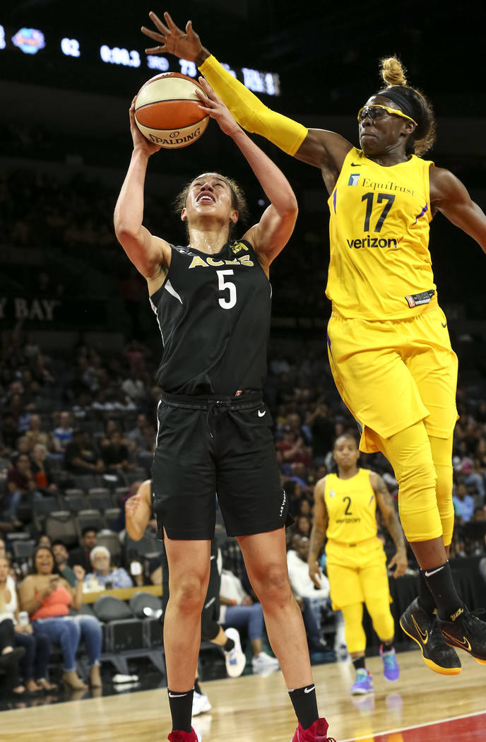 Las Vegas Aces forward Dearica Hamby (5) gets blocked by Los Angeles Sparks forward Essence Carson (17) during the second half of a WNBA basketball game at the Mandalay Bay Events Center in Las Ve ...