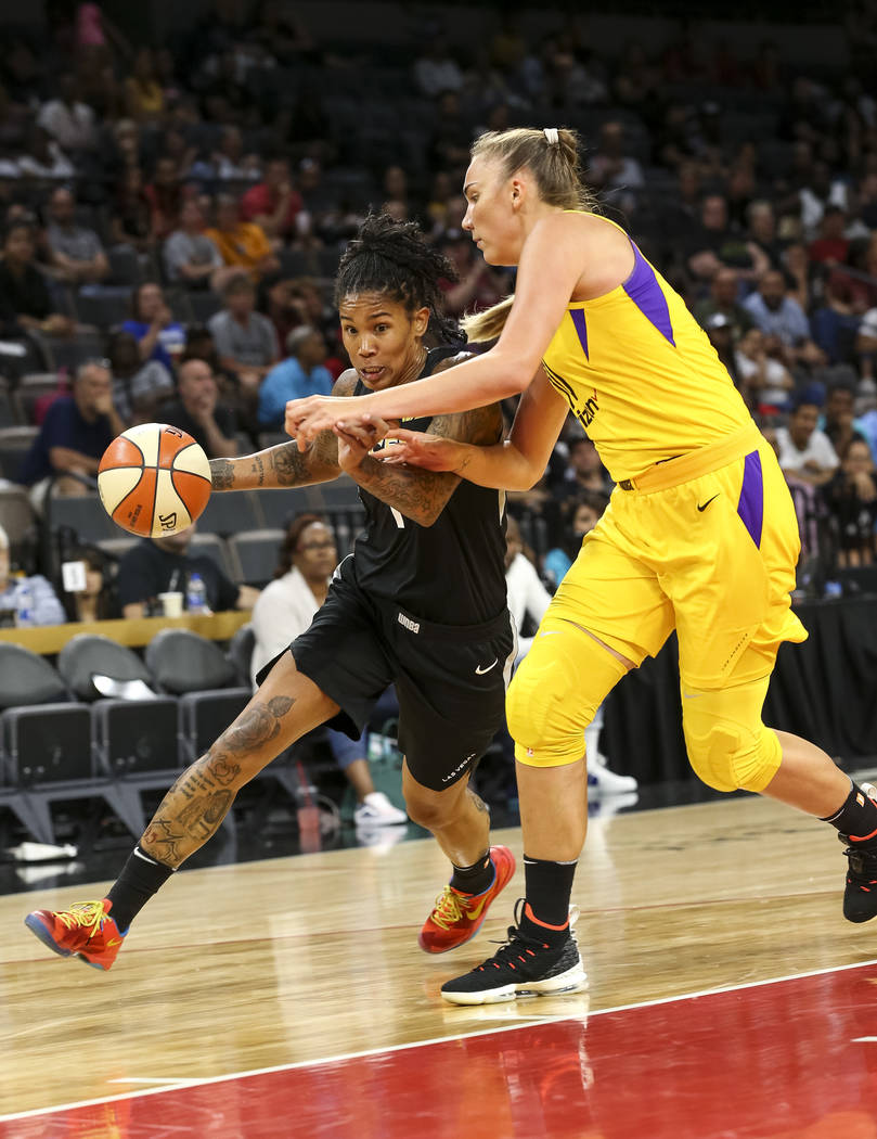 Las Vegas Aces forward Tamera Young (1), left, drives the ball against Los Angeles Sparks center Maria Vadeeva (10) during the second half of a WNBA basketball game at the Mandalay Bay Events Cent ...