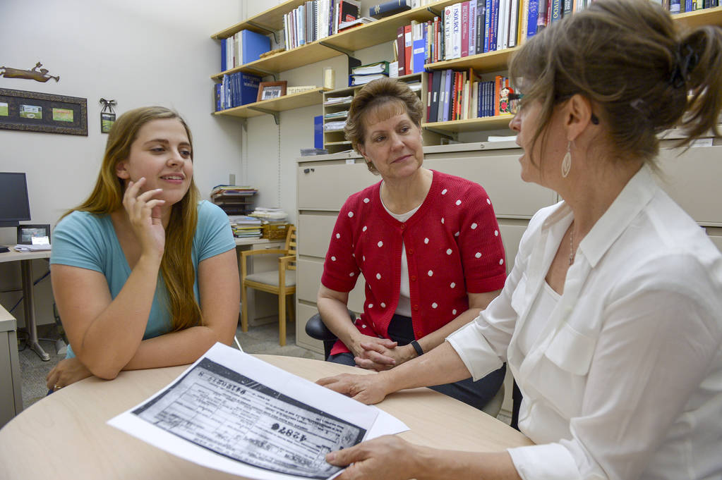 BYU graduate Melanie Torres, left; professor Jill Crandell, director of the BYU Center for Family History and Genealogy, and research fellow Lisa Stokes discuss a missing soldier's case paperwork ...