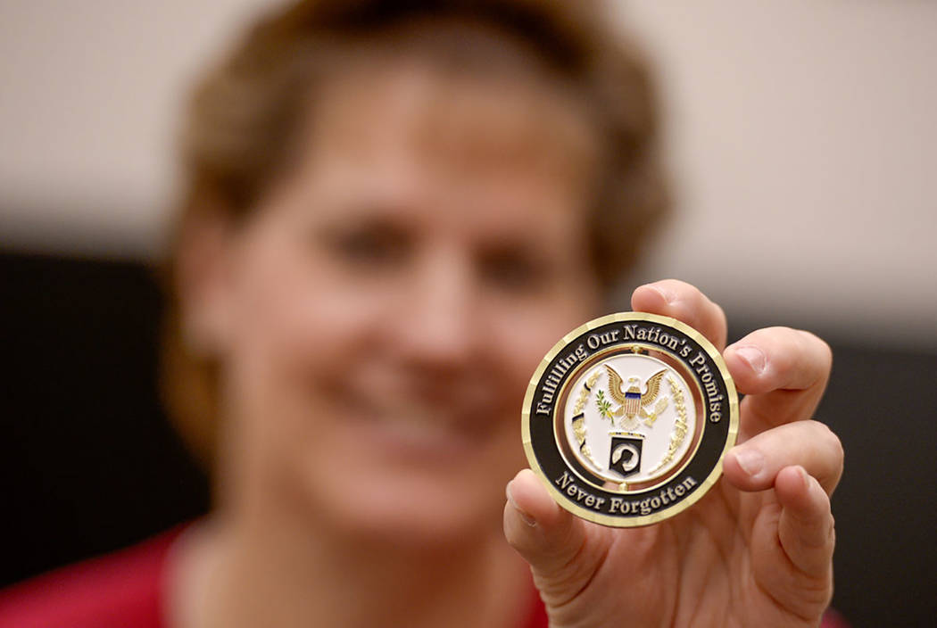 BYU professor Jill Crandell, director of BYU's Center for Family History and Genealogy, holds a challenge coin from the Army and the Defense POW/MIA Accounting Agency (DPAA) on June 21. (Leah Hog ...