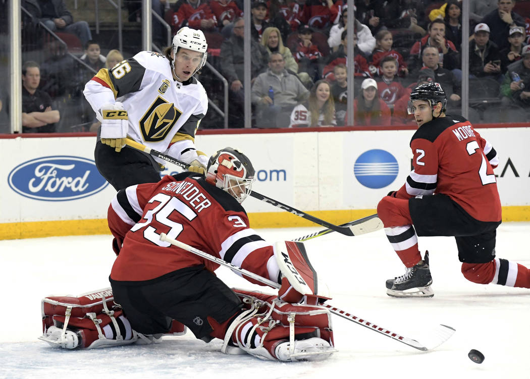 New Jersey Devils goaltender Cory Schneider (35) deflects a shot by Vegas Golden Knights left wing Erik Haula (56) as Devils defenseman John Moore (2) looks on during the first period of an NHL ho ...