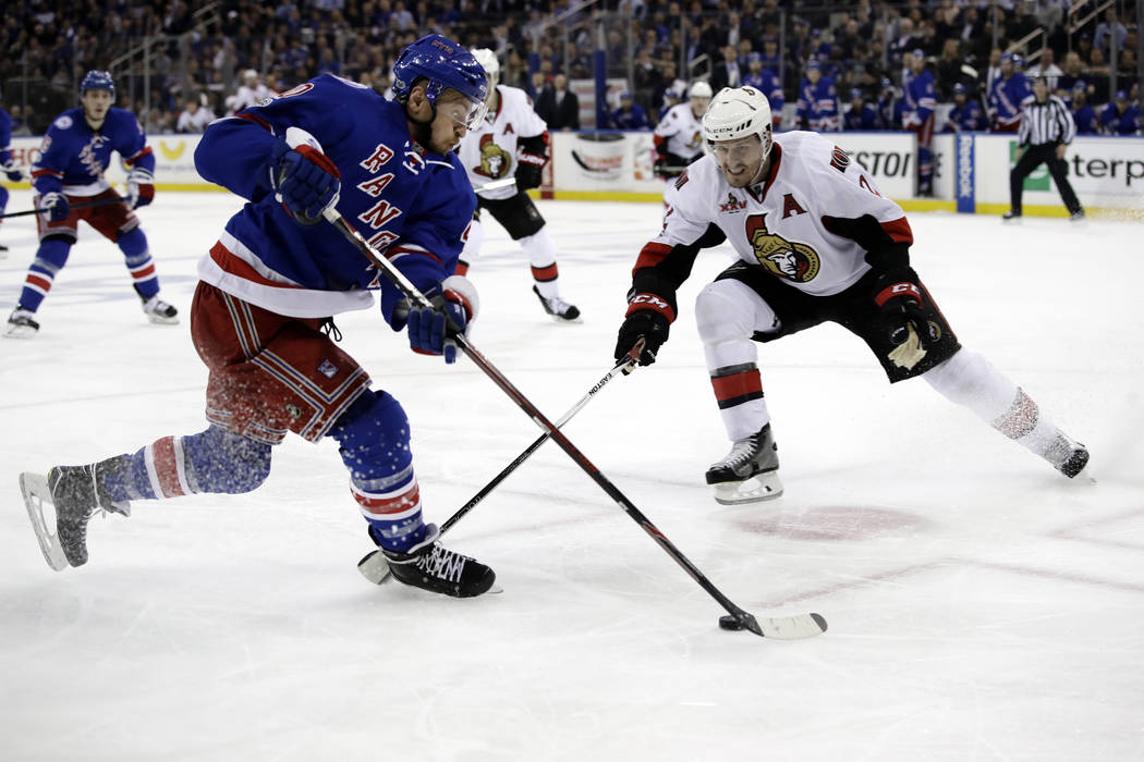 New York Rangers' Michael Grabner (40) looks to control the puck in front of Ottawa Senators' Dion Phaneuf (2) during the second period of Game 3 of an NHL hockey Stanley Cup second-round playoff ...
