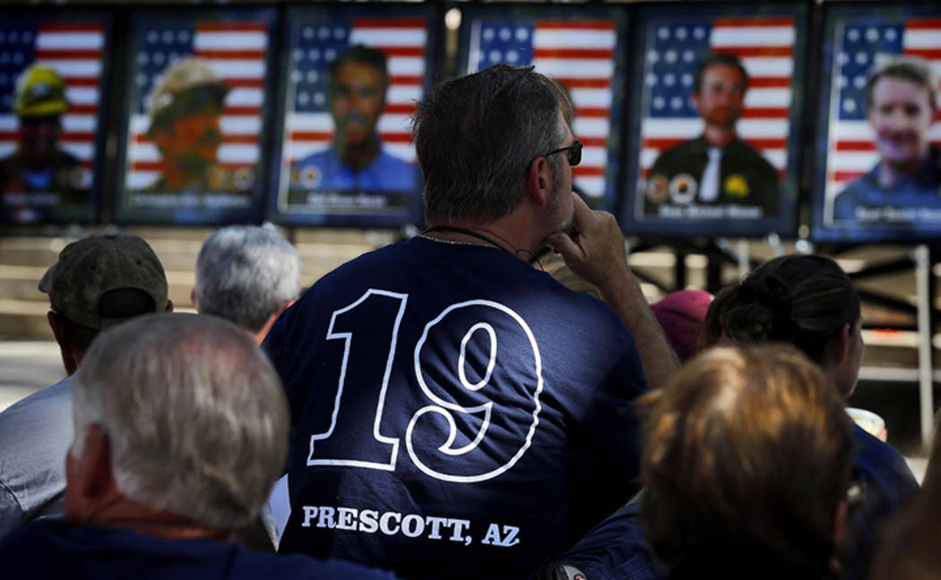 People listen as the 19 Granite Mountain Hotshots are memorialized on the first anniversary of their deaths during a ceremony outside the Yavapai County courthouse in Prescott, Ariz. on June 30, 2 ...