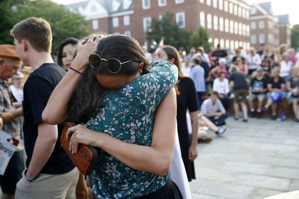 People hug as they gather for a vigil in response to a shooting in the Capital Gazette newsroom, Friday, June 29, 2018, in Annapolis, Md. Prosecutors say Jarrod W. Ramos opened fire Thursday in th ...