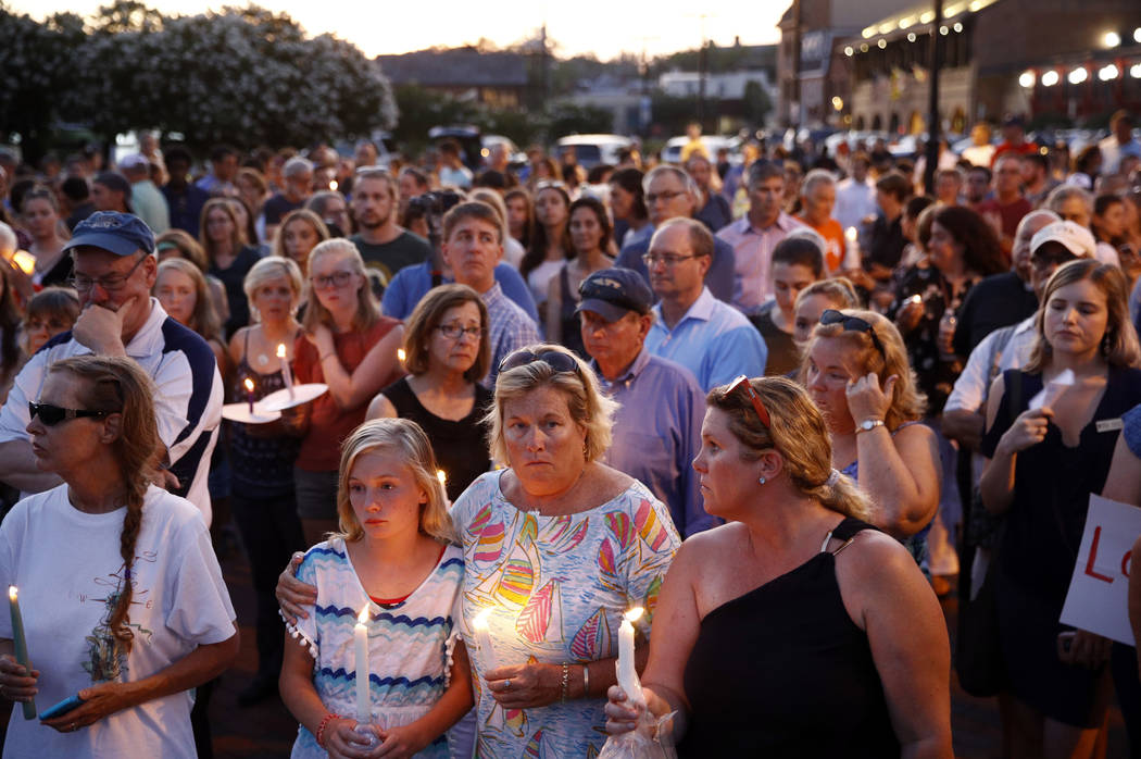 Mourners stand in silence during a vigil in response to a shooting at the Capital Gazette newsroom, Friday, June 29, 2018, in Annapolis, Md. Prosecutors say 38-year-old Jarrod W. Ramos opened fire ...