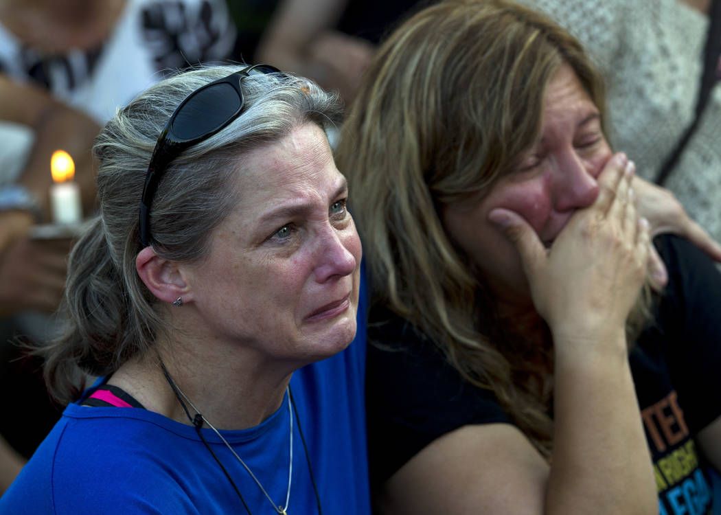 Carol Geithner, left, and Yasemin Jamison gather for a candlelight vigil across the street from where five journalists were slain in their newsroom in Annapolis, Md., Friday, June 29, 2018. Prosec ...