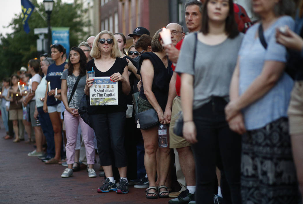 People stand in silence during a vigil in response to a shooting in the Capital Gazette newsroom Friday, June 29, 2018, in Annapolis, Md. Prosecutors say Jarrod W. Ramos opened fire Thursday in th ...