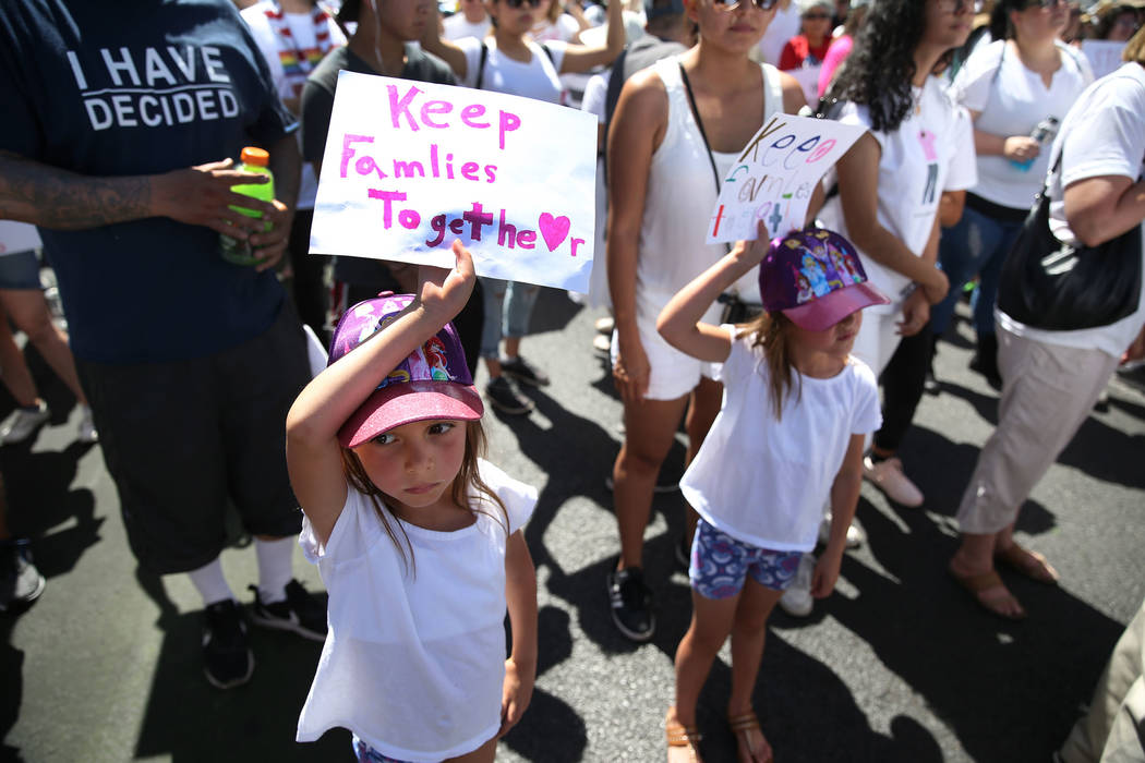 Estella Perkins, left, 7, and her twin sister Sophia, attend a rally against the separation of immigrant families outside of the Lloyd George U.S. Courthouse in Las Vegas, Saturday, June 30, 2018. ...